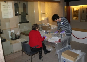Volunteers working in pairs to record and pack objects from the archaeology galleries