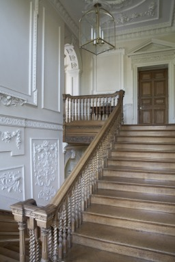 View from the half-landing showing the oak staircase in the Staircase Hall at Mompesson House, Salisbury, Wiltshire. Charles Longueville commissioned the plasterwork decoration in the 1740s.